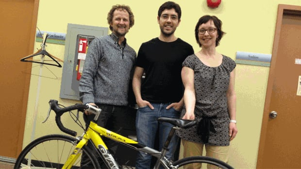 Louis Doucet, of the University of Moncton's department of cultural affairs, Guilherme Ferreira, an international student from Brazil, and Julie Bergeron, of the office of international relations, pose with a donated bike worth $400 they plan to auction off to raise funds for the program that equips international students with used bikes.