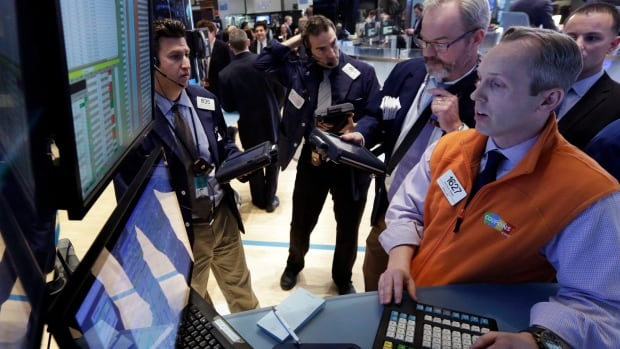 Traders gather at the post of specialist Patrick Kenny, right, on the floor of the New York Stock Exchange. The Dow Jones index posted a record high Wednesday.