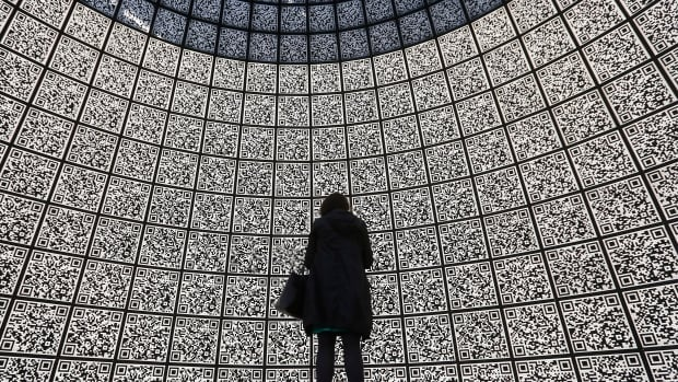 A woman stands in front of QR-code information panels. Data-sharing could, in the future, play an important role in mitigating climate change, according to experts in the field.