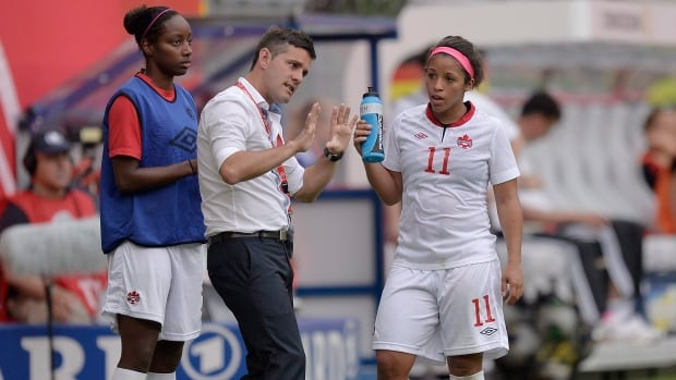 Canada's head coach John Herdman talks to Desiree Scott, right, during an international women's friendly soccer match between Germany and Canada in Paderborn, Germany, on June 19,  2013.