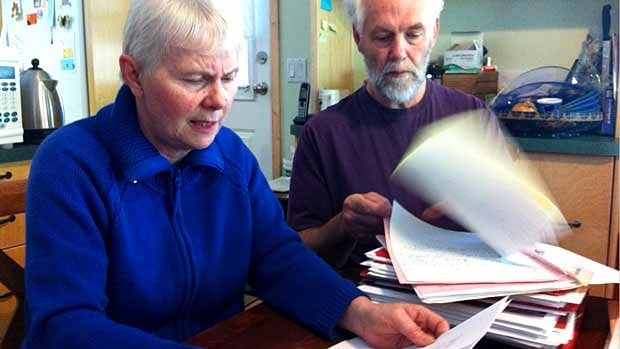 Dave and Sharon Lang pore through a stack of documents relating to the Foreign Worker Program and the Prestige Hotel in Nelson