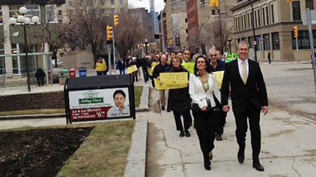 Former Winnipeg city Coun. Gord Steeves walks with his wife and supporters on the way to city hall to file his nomination papers to become a mayoralty candidate.