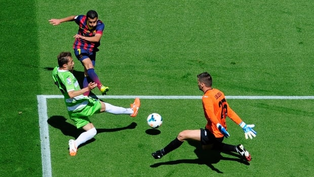 FC Barcelona's Pedro Rodriguez, second left, duels for the ball against Getafe's Rafa Lopez, left, and goalkeeper Julio Cesar, right, on Saturday at the Camp Nou stadium in Barcelona.