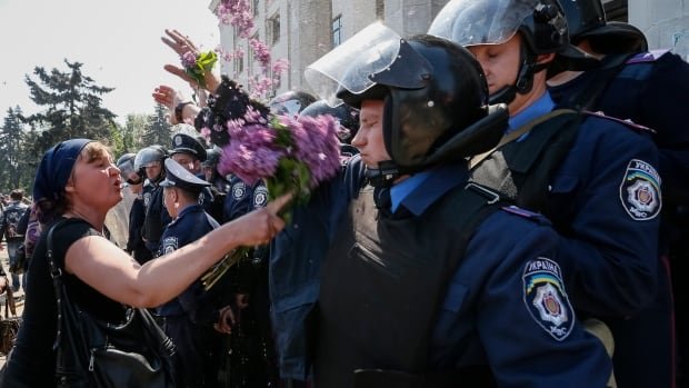 A woman argues with members from the Ukrainian Interior Ministry security forces during a rally outside a trade union building in Odesa on Saturday.