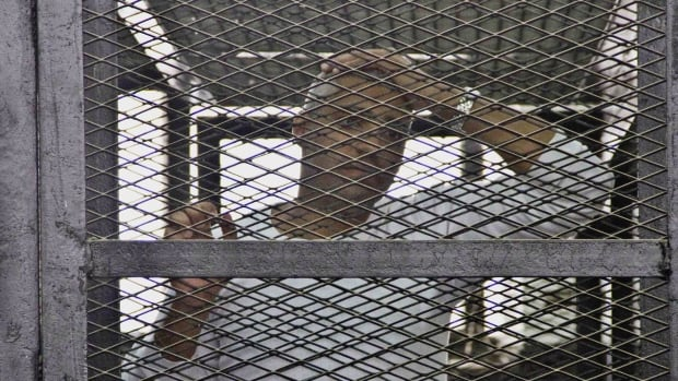 Canadian-Egyptian acting Al-Jazeera bureau chief Mohammed Fahmy appears in a defendant's cage in the Police Academy courthouse along with other defendants during a trial on terror charges in Cairo, Egypt.
