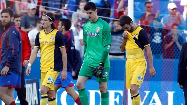 Atletico de Madrid's goalkeeper Thibaut Courtois, centre, Adrian Lopez, right, and Filipe Luis from Brazil reacts against Levante at the Ciutat de Valencia stadium in Valencia.