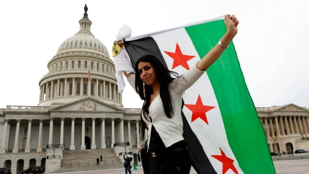An anti-Assad protester carries the Syrian freedom flag in front of the U.S. Capitol in Washington last September. The Obama administration on Monday said it's given approval for the Syrian opposition to open a formal diplomatic mission in Washington, D.C.