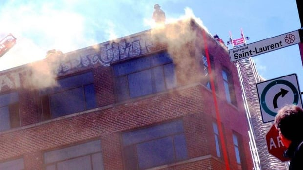 Firefighters fight flames on the roof of 3778 St-Laurent Boulevard.