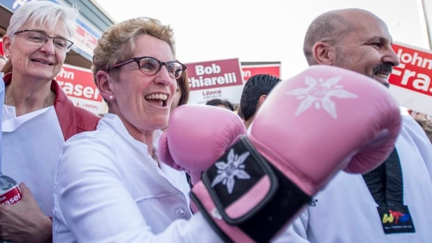 Ontario Liberal Leader Kathleen Wynne shows off a pair of boxing gloves she received as a gift, while her partner Jane Rounthwaite (left) looks on, during a campaign stop in Ottawa South, the riding of John Fraser and former riding of Premier Dalton McGuinty, in Ottawa on Wednesday, May 7, 2014.