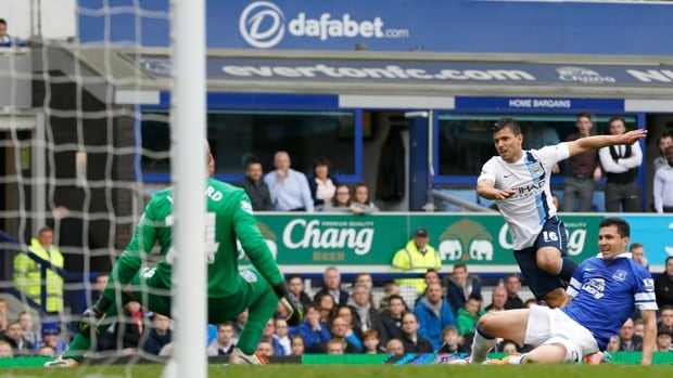 Manchester City striker Sergio Aguero (16) scores on keeper Tim Howard prior to being injured in a 3-2 win at Everton on May 3.