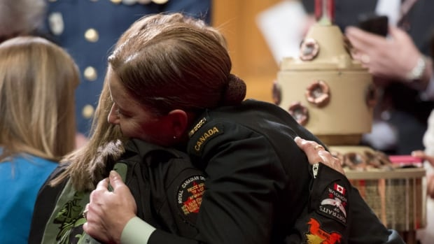Warrant Officer Renay Groves hugs a mother prior to a ceremony in the Senate during a National Day of Honour.