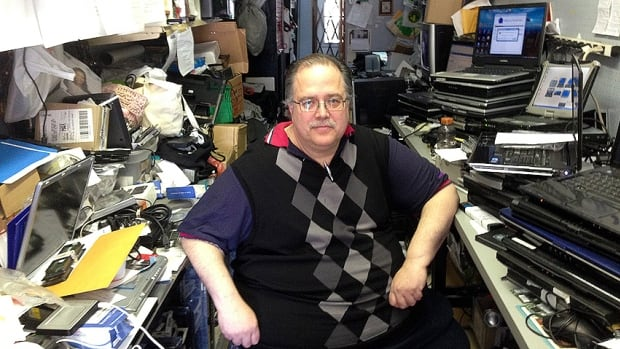 Richard Eckerlin sits in his small computer repair shop in Montreal West. He was recently helped out by residents after his business fell on hard times.