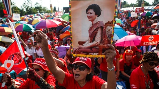 "A member of the pro-government ""red shirt"" group holds a picture of ousted Thai prime minister Yingluck Shinawatra during a rally in Nakhon Pathom province on the outskirts of Bangkok, May 10, 2014. Supporters of Thailand's beleaguered government gathered on Saturday on the outskirts of Bangkok saying they were determined to safeguard democracy and avert a coup as anti-government protesters, based at a central park, planned their ""final push"". Anti-government protest leader Suthep Thaugsuban called his supporters out onto the streets of Bangkok on Friday for what he says will be a final push to get the government out and install an unelected ""people's council"" to oversee reforms aimed at excluding former prime minister Thaksin Shinawatra from politics. REUTERS/Athit Perawongmetha (THAILAND - Tags: POLITICS CIVIL UNREST) - RTR3OJPD"