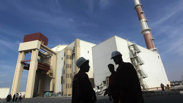 Iranian workers stand in front of a nuclear power plant south of Tehran in October 2010. A United Nations report has revealed how Iran has been evading sanctions, including concealing titanium tubes inside steel pipes, as nuclear talks with world powers continue.