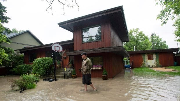 A Bowness resident walks through his neighbourhood of flooded homes after thousands of Calgarians were forced out of the neighbourhood last June. Many homeowners in the area now say finding out details about the current rebuilding rules is not an easy task.