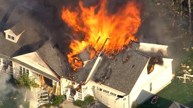 In this frame grab from television helicopter video, a home bursts into flames in Brentwood, N.H., Monday.  Shots were fired just before the fire allegedly at an officer who was responding to a domestic disturbance call at a home.