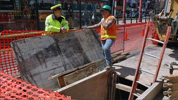 A Toronto police officer, left, works a paid duty assignment at a construction site on Spadina Avenue.