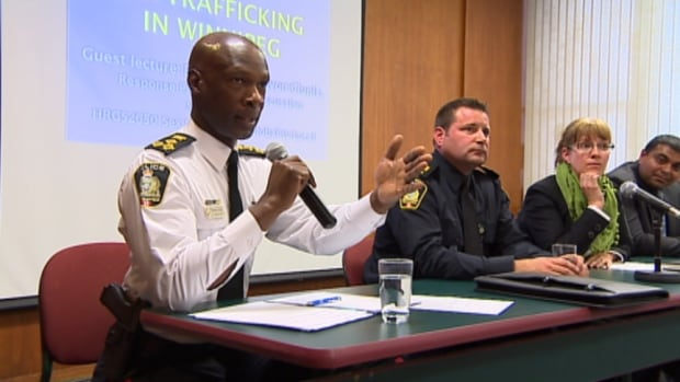 Winnipeg police Chief Devon Clunis, left, speaks at a community forum on Tuesday about what can be done in the city to stop sex trafficking.