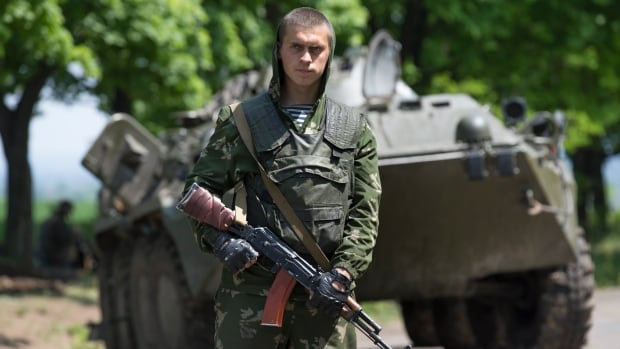 A Ukrainian government soldier guards a checkpoint in eastern Ukraine. The Ukrainian government reluctantly agreed to launch talks on decentralizing power Wednesday as part of a European-backed peace plan.