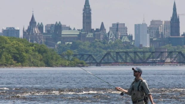 The Parliament buildings are seen behind Drew Lander as he spends his Victoria Day fishing and enjoying the warm weather in the Ottawa River in Ottawa in 2010.