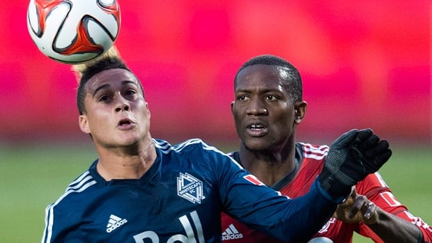Erik Hurtado, left, of the Whitecaps heads the ball away from Doneil Henry in a 2-1 first-leg loss to host Toronto FC on May 7.