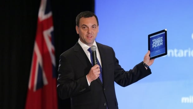 Ontario PC Leader Tim Hudak holds a tablet displaying his party's election campaign platform, dubbed the Million Jobs Plan, during a town hall event in Toronto Wednesday.
