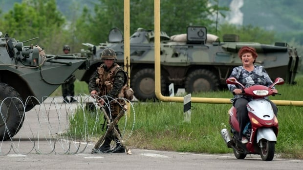 A woman rides a scooter passing a Ukrainian army checkpoint in eastern Ukraine. The army destroyed two military bases of pro-Russian insurgents in overnight operations.