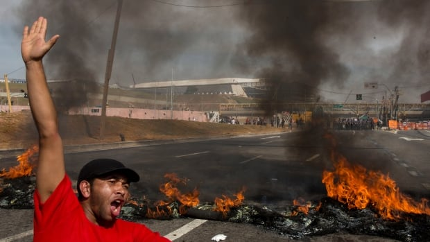 A member of the Homeless Workers Movement protests at a barricade of burning tires against the money spent on the World Cup near Itaquerao stadium on Thursday.