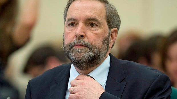 Official Opposition Leader Tom Mulcair adjusts his tie Thursday as he waits to appear before a Commons committee to explain the use of House of Commons resources by the Official Opposition.