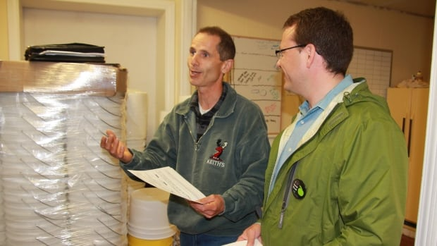 Fergus bee farmer Jim Coneybeare shows Green Party leader Mike Schreiner his past inspection records.