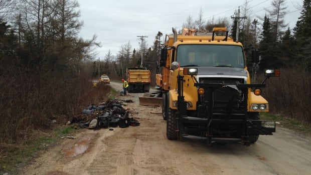 Crews clean trash from Club Road in Harrietsfield on Thursday.