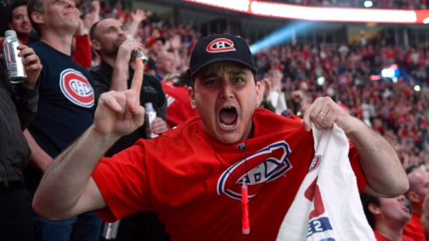 A Montreal Canadiens fan reacts to the NHL action against the Boston Bruins on a giant-screen in Montreal Wednesday May 14, 2014. Montreal's Bell Centre was a sea of red, white and blue on Wednesday night as Canadiens fans packed the arena to watch their beloved Habs play 500 kilometres away.