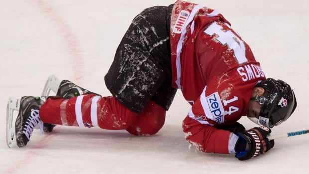 Team Canada Alex Burrows lies on the ice in pain after he collidied with Italy's Joachim Ramoser during first period action on Friday in Minsk.