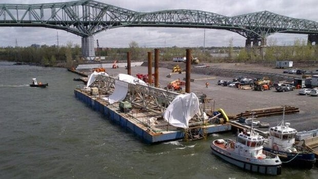 Workers are removing the superbeam from the Champlain Bridge and attaching a steel modular truss with the help of barges on the St-Lawrence.