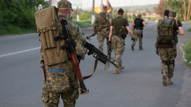 Pro-Russian militants walk to their positions to fight against Ukrainian government troops at a checkpoint blocking the major highway which links Kharkiv, outside Slovyansk, eastern Ukraine.