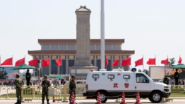 Armed Chinese paramilitary policemen stand guard on the Chang'an Avenue near Tiananmen Square in Beijing Monday, May 12, 2014.