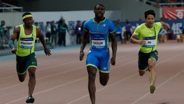 Justin Gatlin, centre, crosses the finish line to win the 100-metre race at the Diamond League meet in Shanghai on Sunday.