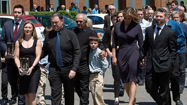 Family members carry the urns of France St-Louis, mother of New York Rangers hockey player Martin St-Louis, right, following funeral service's on Sunday in Laval, Que.