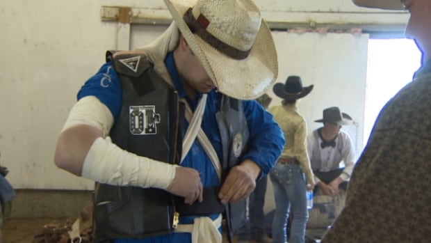 One participants secures a safety vet before competing at the Haymaker Rodeo in Thorsby, Alta.