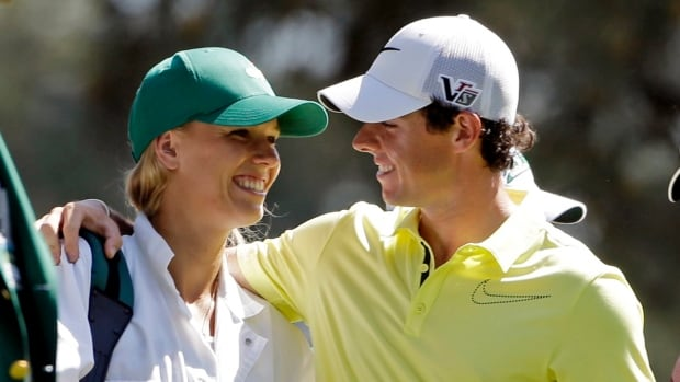 In this April 10, 2013 file photo, Rory McIlroy hugs tennis player Caroline Wozniacki, who was acting as his caddie during the par three competition before the Masters.