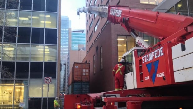 Crews put shipping containers in place to form a heavy barricade wall in case more bricks or debris fall from the building.