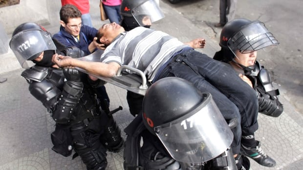 Riot police carry a passerby who fainted during a protest in front of the National University in Bogota, Colombia, on May 20, 2014. Canada's NDP and civil society groups are accusing the Harper government of whitewashing human rights abuses in the country in the latest report to Parliament on the impact of Canada's free trade agreement with Colombia.