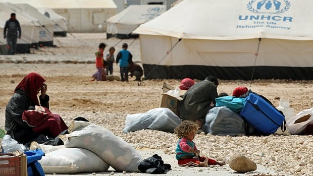 Newly arrived Syrian refugees sit with their received aid and rations while waiting for their tent to be built at the Al-Zaatri refugee camp in the Jordanian city of Mafraq, near the border with Syria, in April 2014.