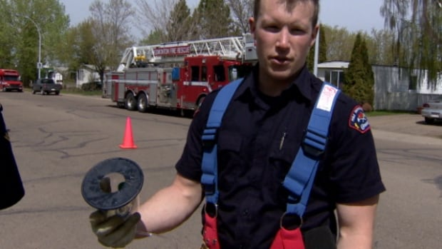 Firefighter Adam Selinger shows the oxygen mask used on Bella.
