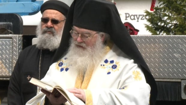 A clergyman reads scripture during the ceremony.