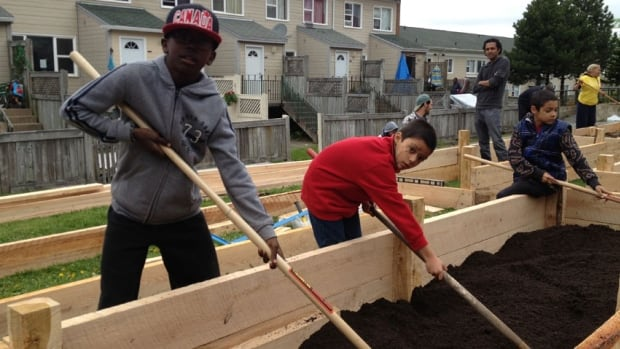 Ten-year-old Ajahni Cadougan prepares soil along with Felipe Sanchez, 8, at the new Mulgrave Park community garden.