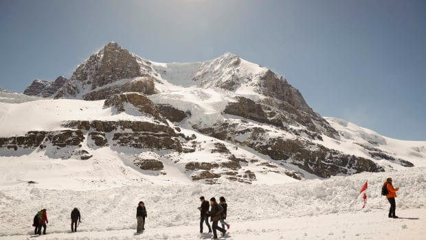 Tourists walk on the Athabasca Glacier, part of the Columbia Icefield in Jasper National Park, on May 7, 2014. Alberta's glaciers are under threat from a changing climate.