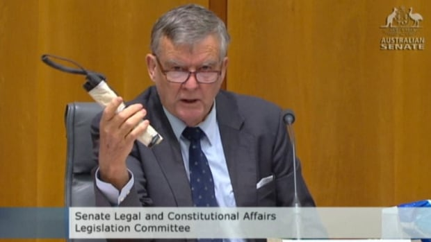 Sen. Bill Heffernan shows a fake pipe bomb during a committee hearing in Canberra, Australia, Sunday, May 25, 2014.