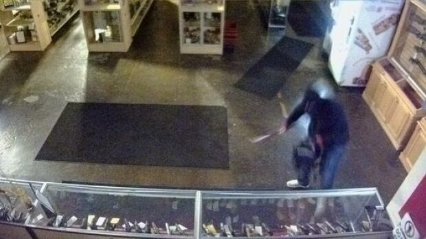 Police are looking for a man who is seen on security video smashing display cases before stealing 11 handguns at the Shooting Range in southeast Calgary on May 11.