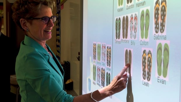 Ontario Liberal Leader Kathleen Wynne checks student attendance on a smart board during a visit to Holy Cross school in Sault Ste. Maire, Ont. during a campaign stop on May 27, 2014.